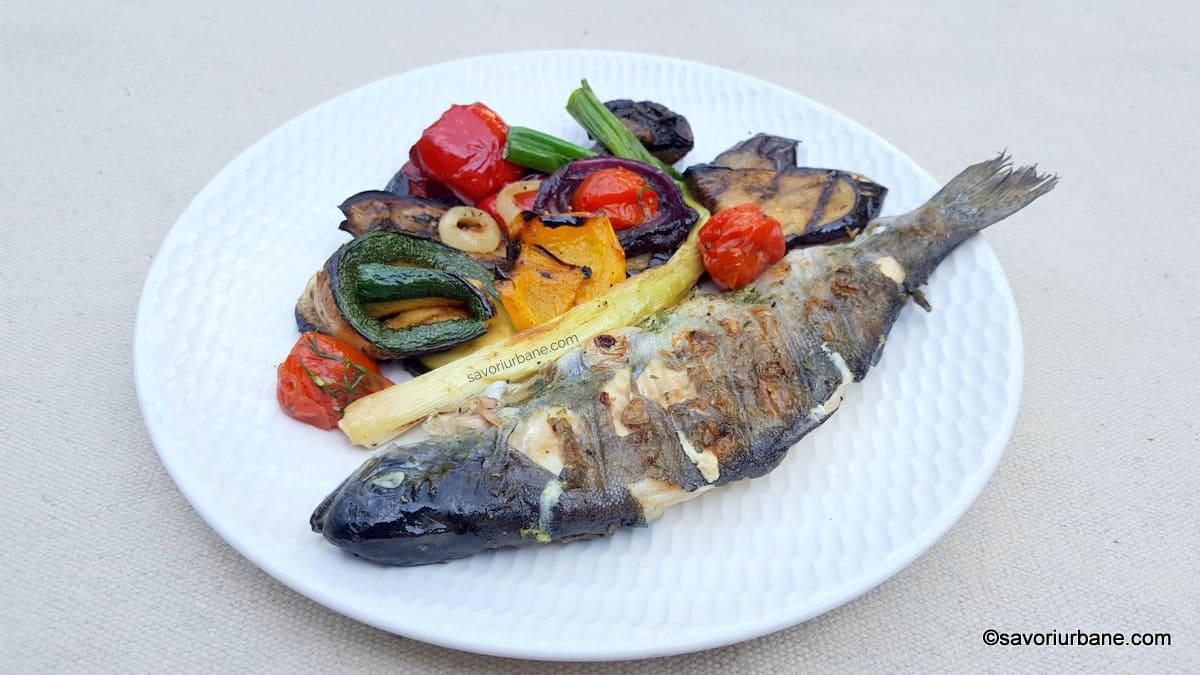 Pastrav la gratar marinat si umplut cu usturoi, unt si verdeturi reteta savori urbane